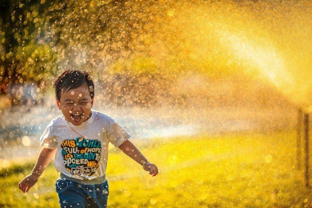 Bimbo che ride e gioca con l'acqua